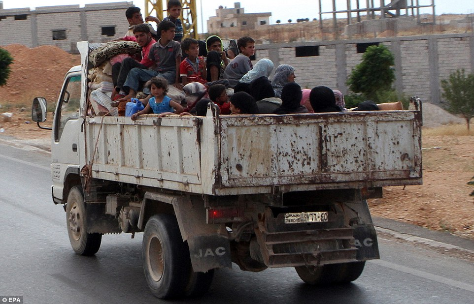 Syrian refugees ride a  truck towards Syria through the Masnaa checkpoint from the Lebanese town of Arsal near the Syrian border, in the Bekaa Valley, Lebanon, yesterday, after a truce was announced to end fighting between the Lebanese army and Islamist militants on the Syrian border