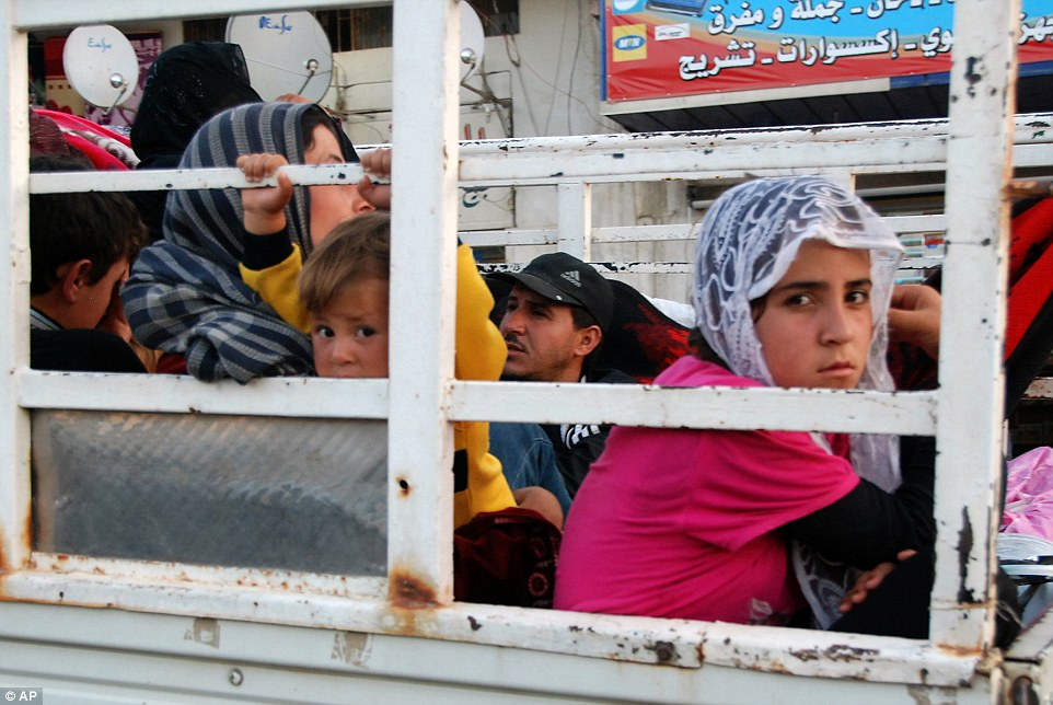 Syrian refugees flee from the Lebanese eastern town of Arsal on their way to cross back into Syria, as they ride in the back of a pickup truck with their belongings at the Lebanese border crossing point of Masnaa, eastern Bekaa Valley, Lebanon, Thursday