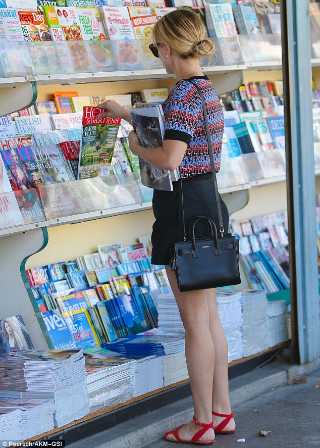 A bit of light reading: The Legally Blonde star stops at a news-stand on her way home