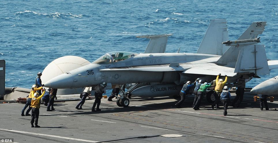 It begins: One of the two F/A-18C Hornet fighter jets that bombed the ISIS artillery position prepares for takeoff from the USS George H. W. Bush in the Persian Gulf before the dawn mission this morning