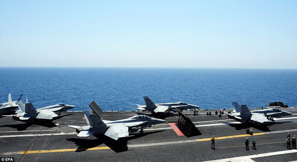 Ready for action: And as soon as the first two jets returned from their successful bombing run on ISIS fighters marching on Erbil this morning, the flight deck of the George H. W. Bush aircraft carrier came alive as more warplanes readied for action