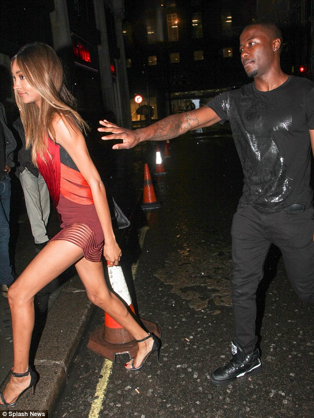 Protective: Jourdan's brother puts his arm towards his sister as they go into the club