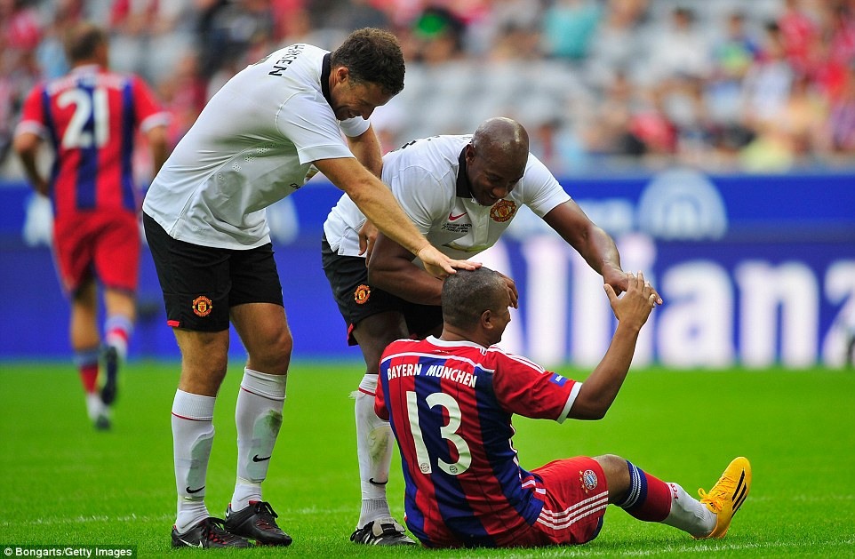 Not too serious: Ronny Johnson and Dion Dublin joke around as they try to keep Bayern's Paulo Sergio on the floor to stop him from scoring again