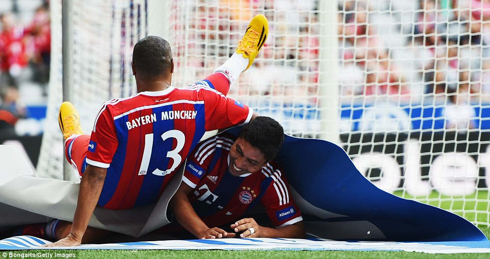Strange way to celebrate: Giovane Elber rolls up in a sponsor's sign while Paulo Sergio joins him in celebrating his goal that put Bayern 2-1 ahead in Munich
