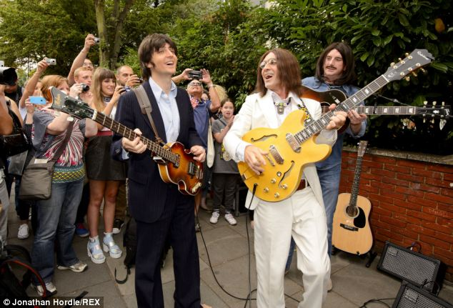 Performance: Two cast members are seen singing beside the crossing, situated near Abbey Road Studios