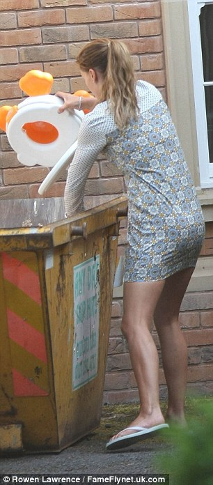 Out with the old, in with the new: The 30-year-old was seen taking a number of items to the skip that was parked outside her home
