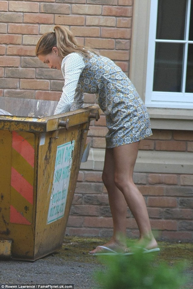 Digging deep: The mother-of-three flashed her pins in a patterned mini-dress during her clear-out