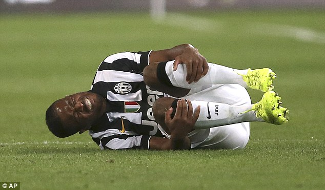 Trouble? Patrice Evra writhes around in agony after picking up a knock during the win