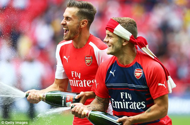 Champagne showers: Ramsey enjoys the first silverware of the season with Jack Wilshere at Wembley
