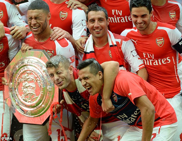 Shut your eyes: Arsenal celebrate lifting the Community Shield after beating Manchester City 3-0 at Wembley