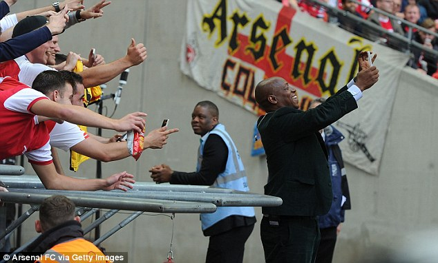 Suited up: Ian Wright, taking a selfie with Arsenal fans, was back in a suit after his World Cup wearing shorts