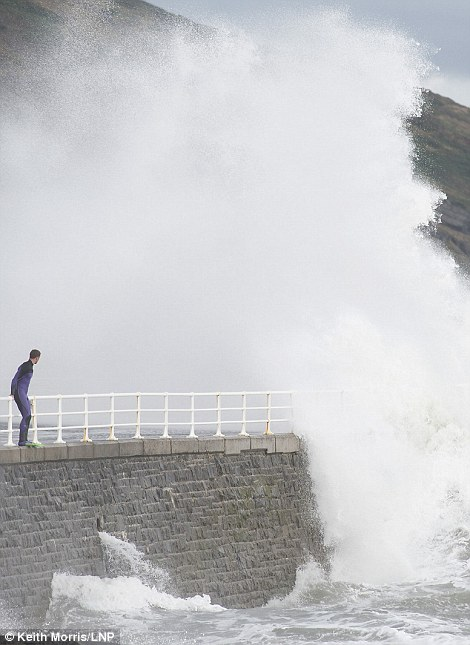 Dangerous: A man prepares to jump into stormy waters at the seafront and harbour of Aberystwyth on the west Wales coast