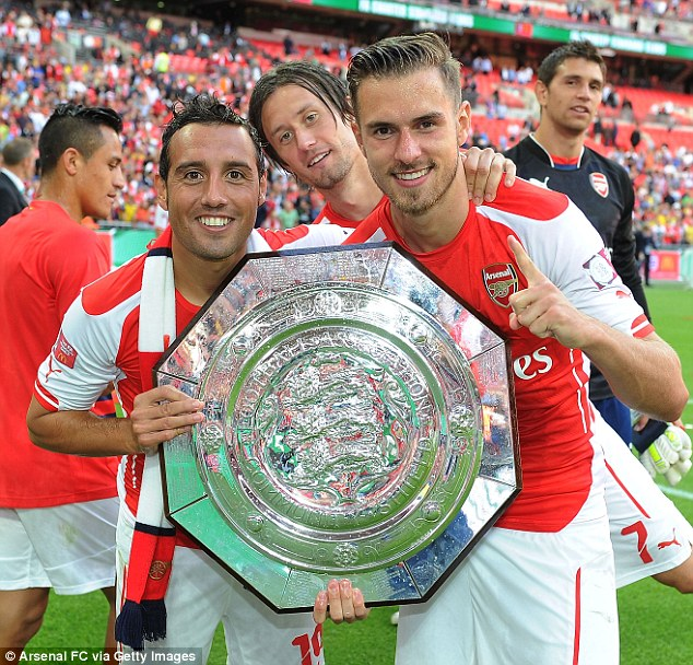 More, more, more: Ramsey (right), with Santi Cazorla and Tomas Rosicky, is eager for more silverware