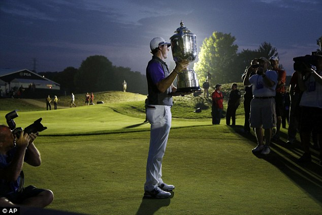 In the spotlight: McIlroy shows off his latest piece of silverware to the cameras