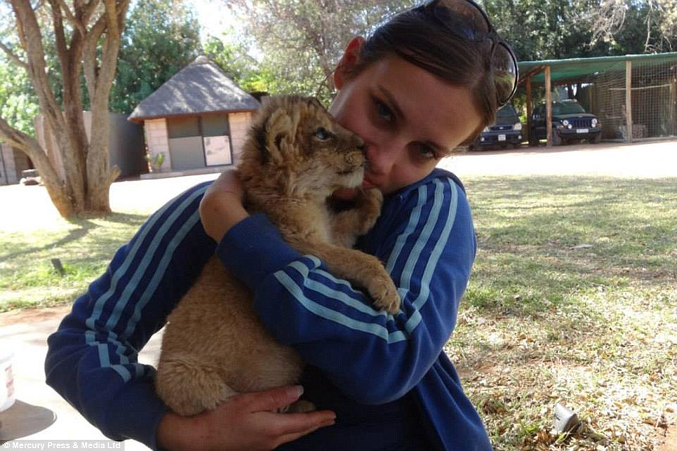 Lion hug: Goska cradles a baby lion in her arms in one of the many amazingly cute photos in her collection