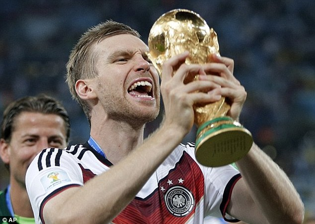 Joy: Arsenal centre back Per Mertesacker grasps the World Cup after winning the trophy in Brazil