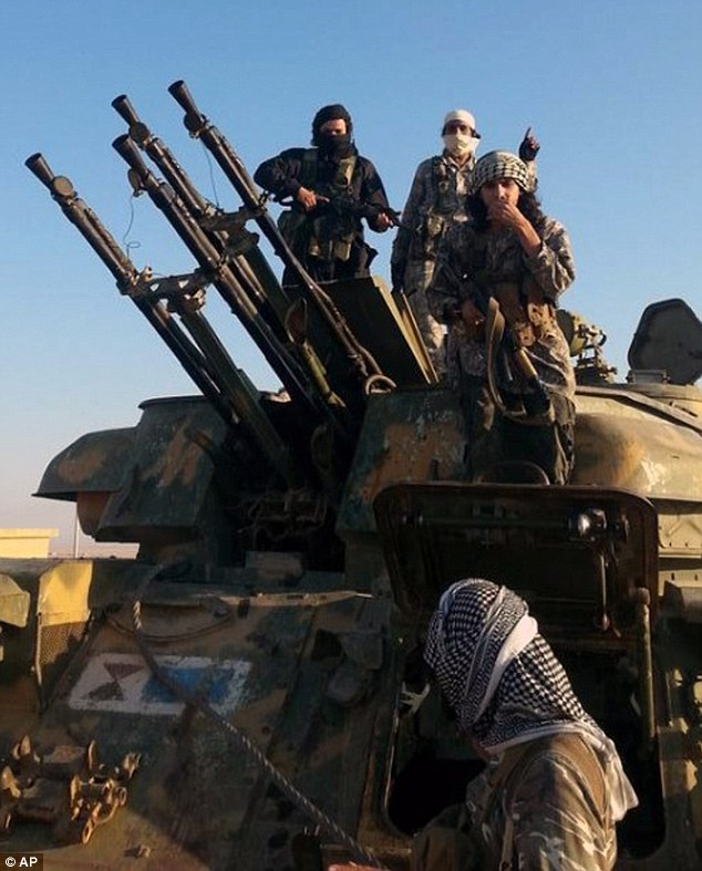 Fighters from the Islamic State group stand on top of a military vehicle with anti-aircraft guns in Raqqa