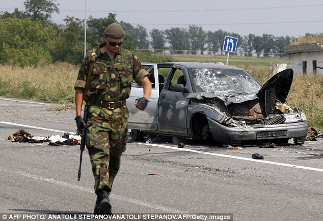 A Ukrainian soldier walks past a wrecked car used by pro-Russian militants who tried to break through the checkpoint of Ukrainian forces, near the eastern Ukrainian city of Donetsk today