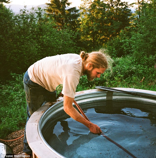 Finishing touches: A friend gets the hot tub ready after it was built from the ground up using local wood