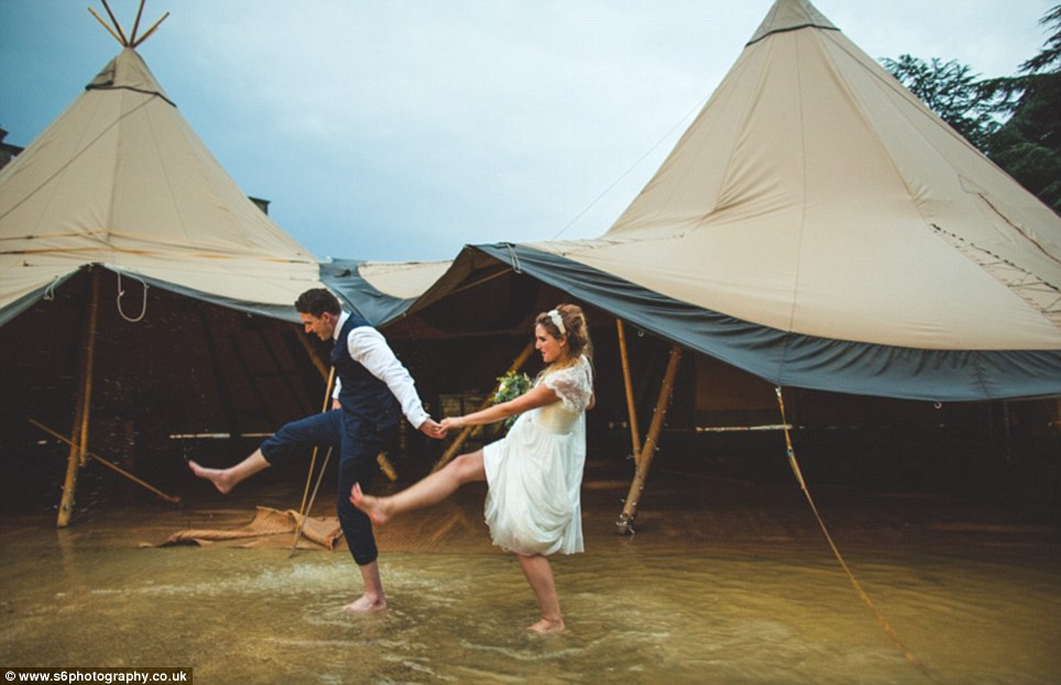 It wasn't the most conventional first dance... but the couple kicked their feet in unison as they danced together in the rain