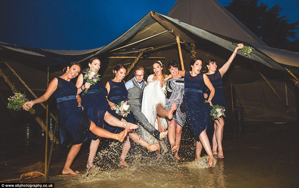 The bridesmaids hitched up their skirts and waved around their bouquets as they danced with other guests in the water