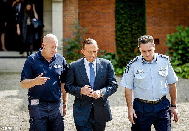 Mr Abbott walking with two Australian forensic researchers during a visit to the Korporaal Van Oudheusden barracks in Hilversum, where the victims are being identified