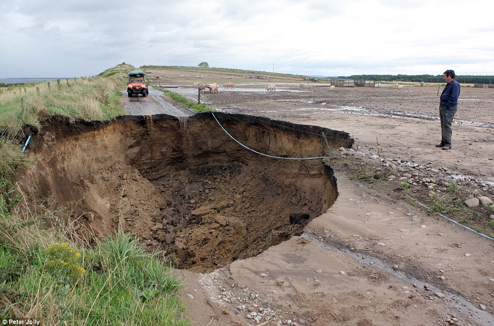 Farmer Brian Mutch looks at a huge sink hole which has opened up on his farm road at Delnies, near Nairn, since the start of the storm