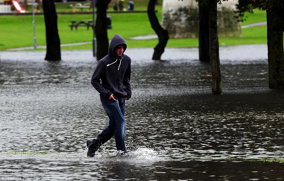 Councils across Britain face a hard task trying to clear up the aftermath of the storm, which has caused widespread flooding across many parts of the UK, including Scotland. Pictured: A man walks through flooding in Elgin, Moray