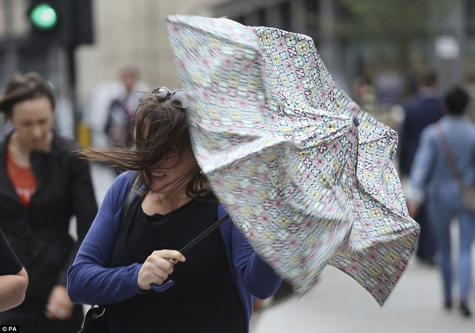A pedestrian grimaces as a gust of wind and torrential rain hammers down in central London. Although the south east will have the best of the country's weather, forecasters still say heavy showers could stick around until Friday