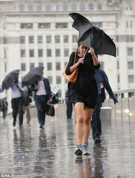 City workers walking along London Bridge toward the station during a rain shower