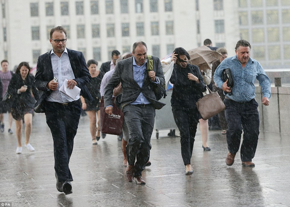 Making a run for it: City workers walking along London Bridge towards the station during a rain shower