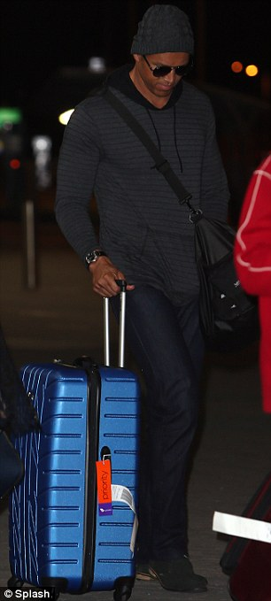 Travelling in style: Blake slung a black bag over his shoulder while wheeling along a blue suitcase