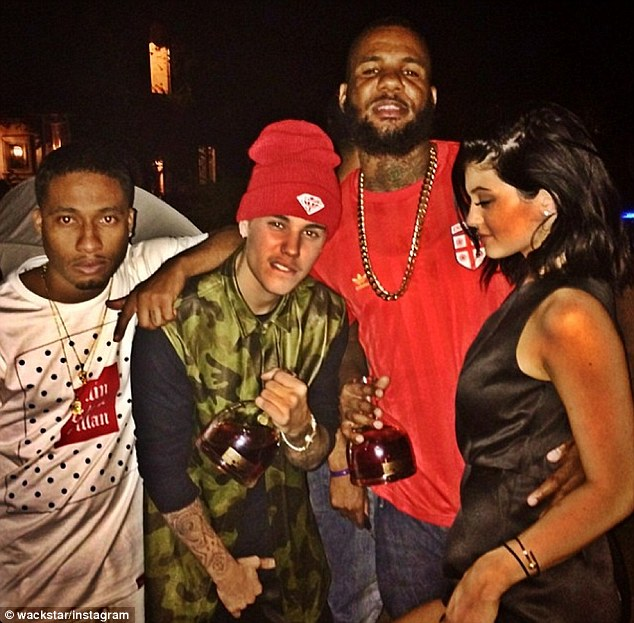 Not yet 21: Kylie (far right) celebrated turning 17 on Saturday night at an LA club with (from left) Tyga, Justin Bieber and The Game, the last two who were holding bottles of hard liquor