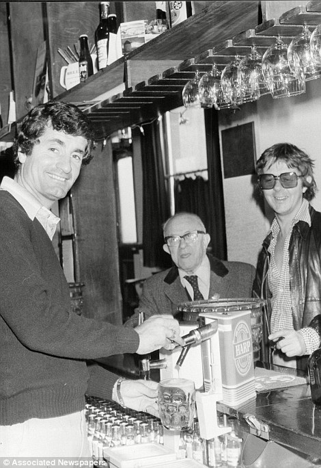 Former Arsenal Footballer Frank McLintock pulls a pint behind the bar of his pub, The Sutton Arms in Islington