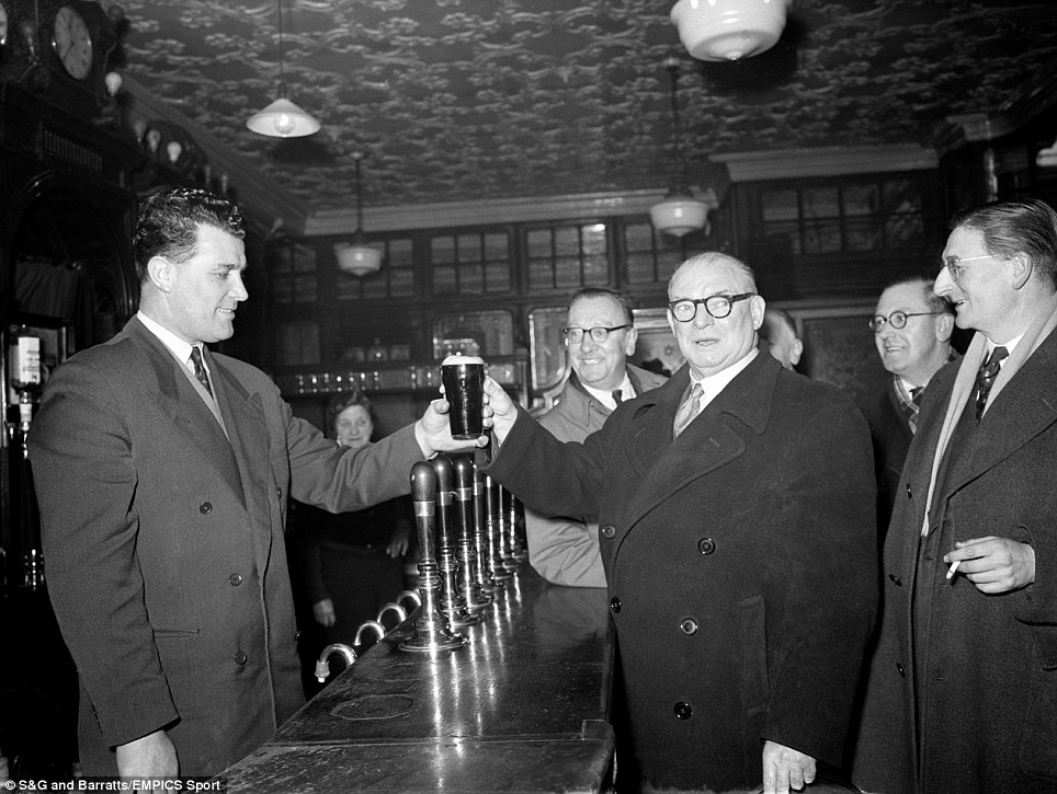 Leslie Compton serves a pint to Arsenal manager Tom Whittaker, in Compton's pub, the Hanley Arms in North London
