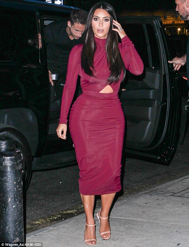 Revealing in red: Kim Kardashian showed off her curves in a sexy maroon dress as she stepped out for dinner in New York on Monday night