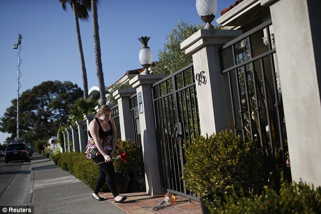 Thank you for the laughter: A woman leaves flowers outside the home of actor and comedian Robin Williams in Tiburon, California August 11, 2014