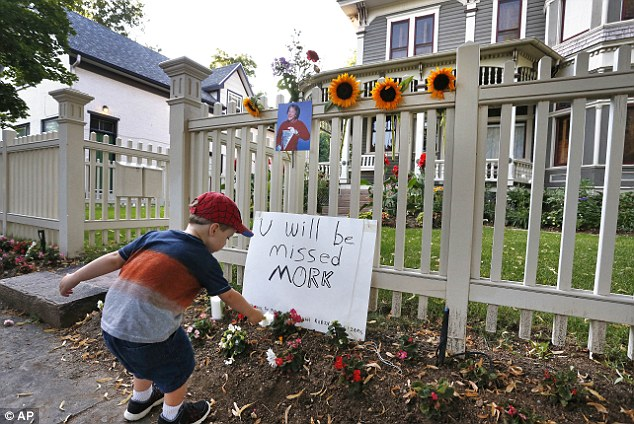 """Touching: AJ Polis leaves a flower alongside a placard and a photo of the late actor Robin Williams as Mork from Ork, as people pay their respects at the home where the 80's TV series """"Mork & Mindy"""",was set, in Boulder, Colorado"""