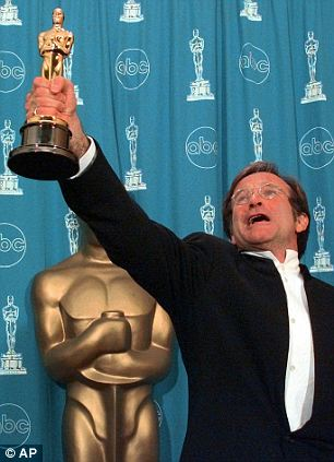 """FILE - This March 23, 1998 file photo shows Robin Williams holding his Oscar high backstage at the 70th Academy Awards at the Shrine Auditorium in Los Angeles after won Best Supporting Actor for """"Good Will Hunting."""" Williams, whose free-form comedy and adept impressions dazzled audiences for decades, has died in an apparent suicide. He was 63. The Marin County Sheriffís Office said Williams was pronounced dead at his home in California on Monday, Aug. 11, 2014. The sheriffís office said a preliminary investigation showed the cause of death to be a suicide due to asphyxia. (AP Photo/Reed Saxon, File)"""