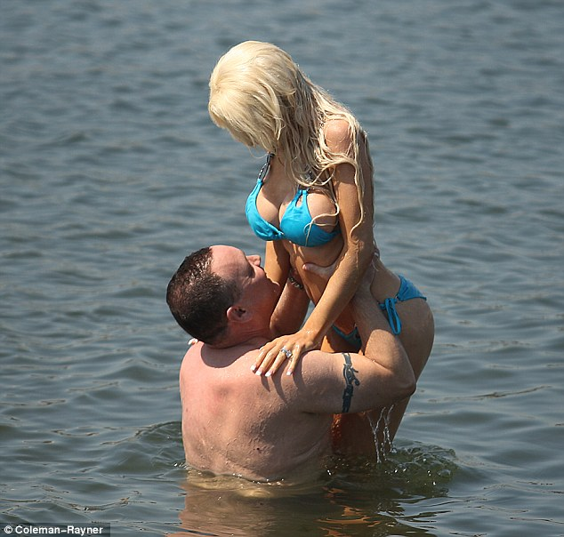 Hold on: The surgically enhanced teenager frolicked in a blue bikini as she locked lips and canoodled with her 35 years older main man