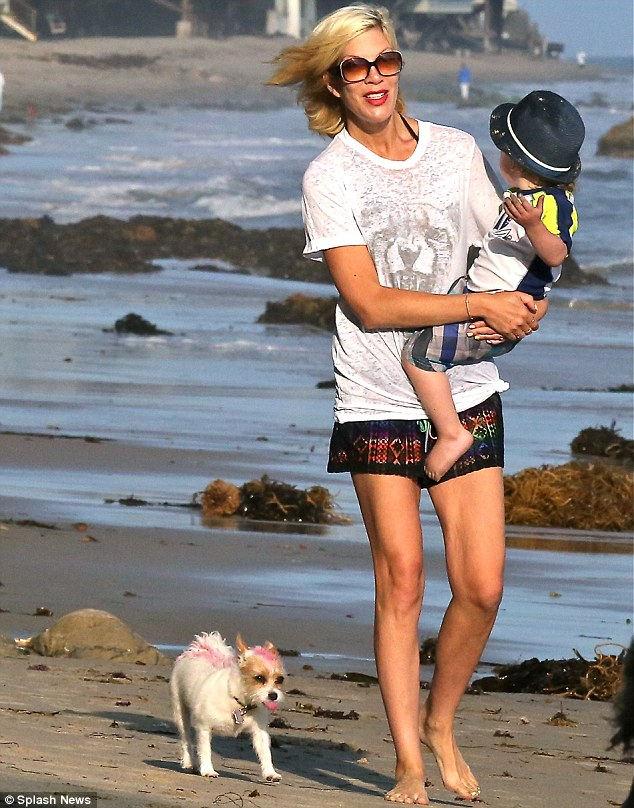 Fun in the sun: Tori Spelling, 41, was spotted during a family outing at the beach in Malibu on Monday while closely followed by her adorable dog