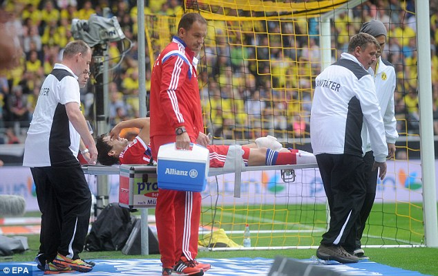 Painful: Javi Martinez is carried off the field on a stretcher after suffering the injury