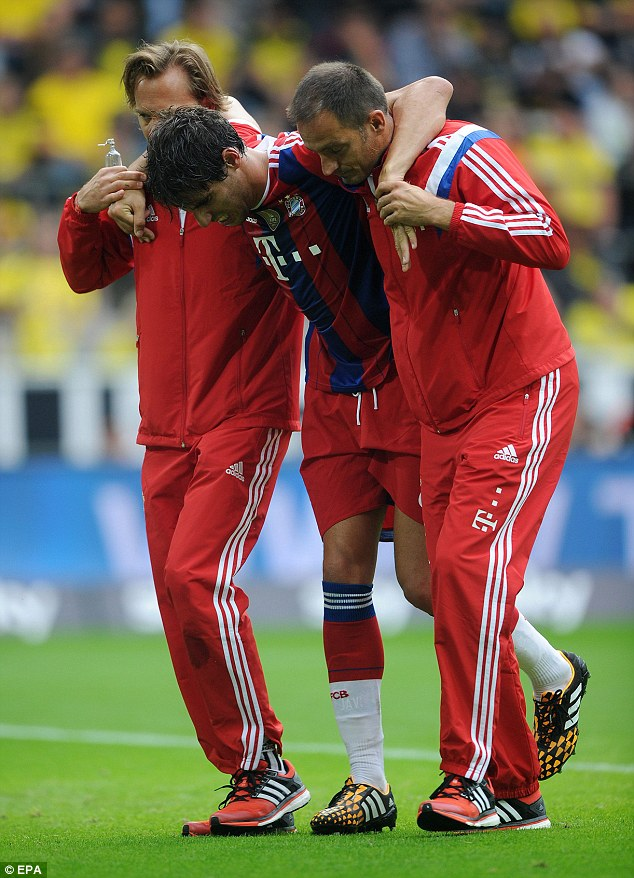 Helping hand: Two members of the Bayern support team help remove Martinez from the pitch