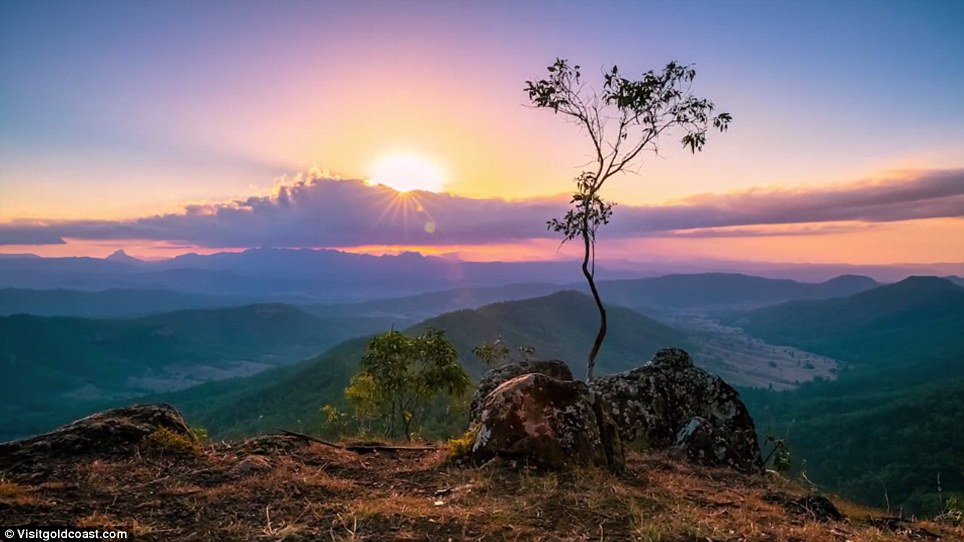 Sunset is viewed from high atop a mountain overlooking the valleys below