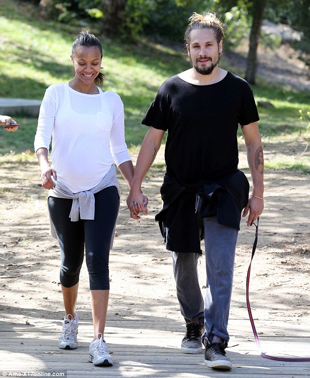 I got you babe: Zoe was glowingly radiant during her stroll and didn't want to let go of Marco's hand either