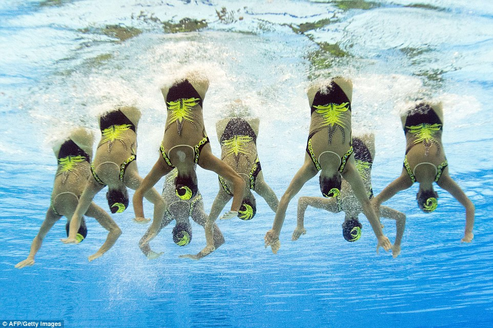Striking a pose: An underwater camera captures the incredible poise of Italy's synchronised swimmers as they twist their bodies upside down in unison and point their legs out above the surface