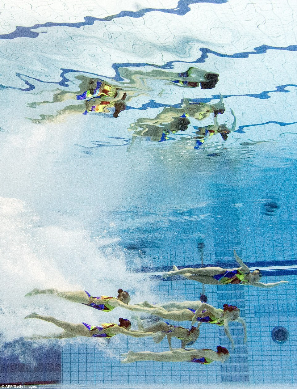 Diving deep underwater in the performance pool in Berlin, Russia's team line up another move. A wavy reflection of their manoeuvre can be seen on the surface