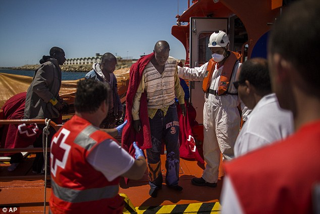 Members of the Spanish Red Cross and rescue service team help a migrants after being rescued together with another ten men  at the Strait of Gibraltar near the coast of Tarifa, southern Spain