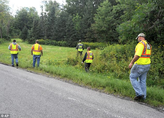 Search: Officials search a roadside field after the girls vanished; a witness said he saw a white car near their stand