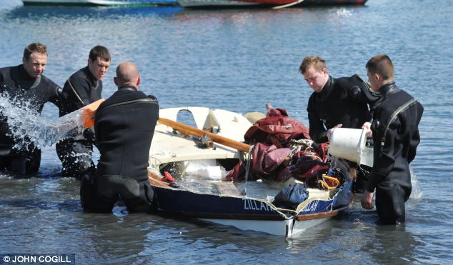 Douglas Perrin, 66, drowned when his boat capsized near Sherkin Island, off the coast of County Cork (pictured, divers haul the wreckage of the craft shore)